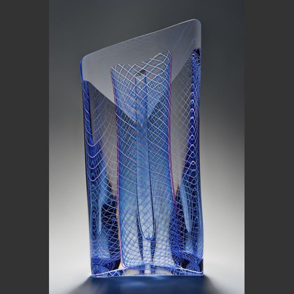 art glass sculpture with blue mesh pattern in dress shape caged in outer clear glass structure