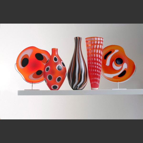 collection of five red art glass sculptures in different shapes with black and white patterns