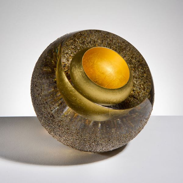 contemporary art glass sculpture of a sphere in earthy colours and layers showing golden core
