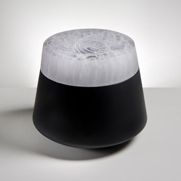 urn shaped modern cast glass sculpture with black base and white patterned top