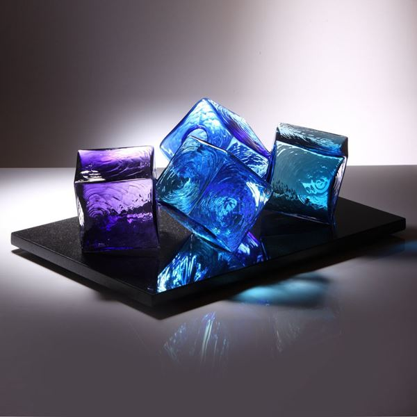 artwork of light and dark blue and purple glass cubes on black rectangular base