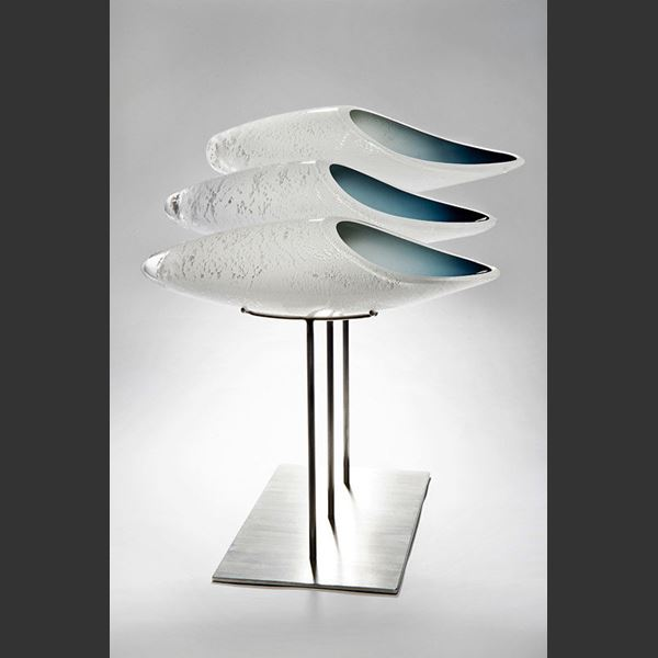 three fish shaped white glass sculptures on metal base