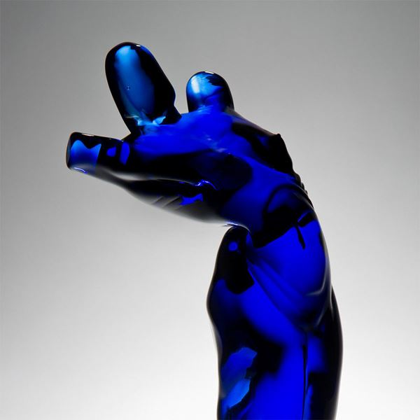 abstract blue glass sculpture of body-like shape on black base