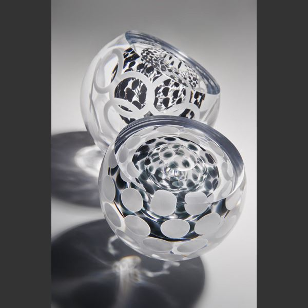 two small round glass artworks in clear glass with edged cut and circular pattern in white