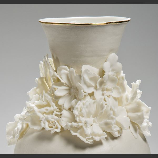 modern ceramic vase sculpture of a classical style in white with flowers sculpted at neck