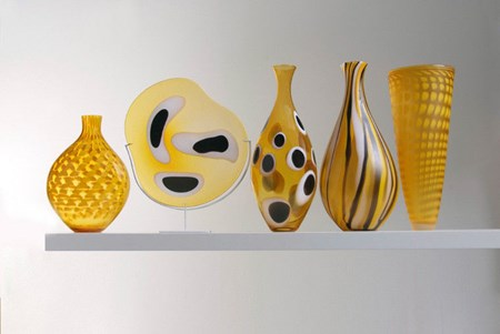 five handblown glass vases in shades of yellow with various patterns