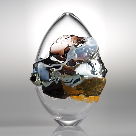 modern oval shaped art glass sculpture with graffiti like external decoration