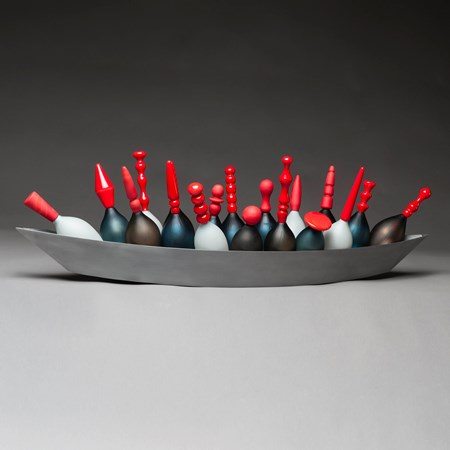 artwork of red topped glass skittles in long steel tray