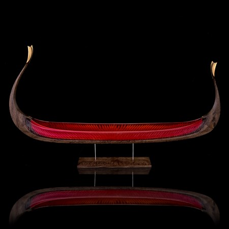handblown glass and carved wood sculpture of viking ship in red and dark brown