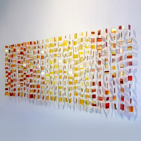 wall hanging glass installation made from small orange, yellow and red pieces
