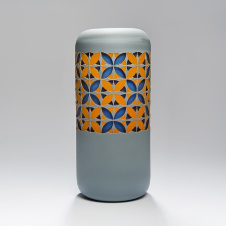 tall art glass sculpture in grey with orange and blue pattern