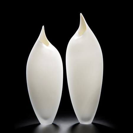two minimalist art-glass sculptures in white shaped like birds