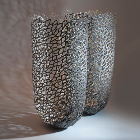 two modern art sculpted vessels made from steel and gold
