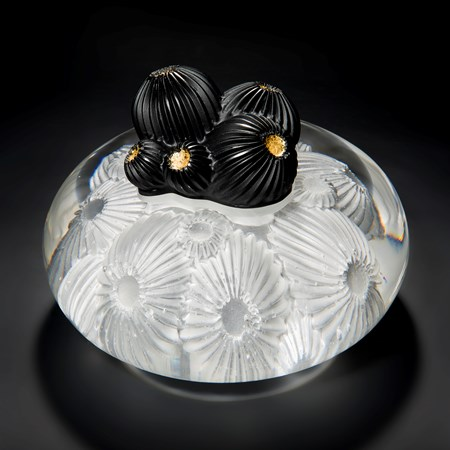 glass artwork of white star coral with round black berries in centre