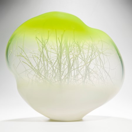 orb shaped glass art sculpture with internal tree branch like structure with white base and bright yellow top