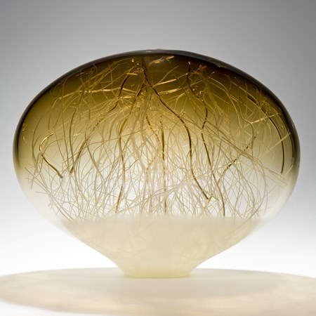 orb-shaped green and beige coloured glass sculpture with delicate nature-inspired internal structure