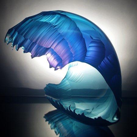 sculpted glass artwork in the shape of a wave with different shades of blue