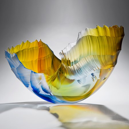 glass art sculpture in the shape of a wave in shades of yellow orange and blue