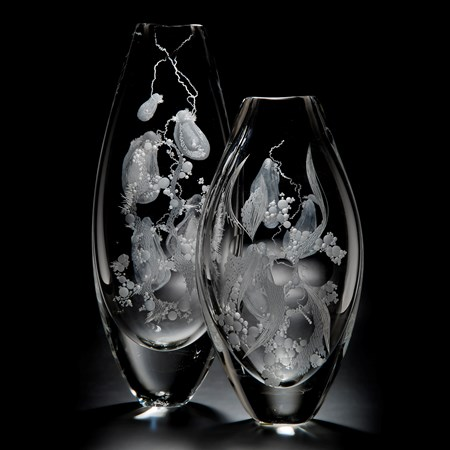 two clear glass vases with engraved flower patterns