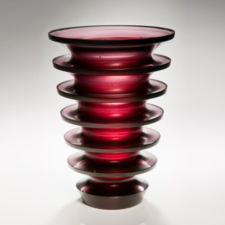 tall dark red art glass sculpture with geometrically positioned rings