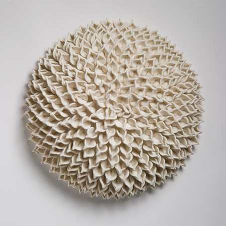 wall hanging geometric looking ceramic artwork of flowers in white