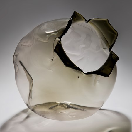 grey art glass sculpture of round fruit with open end