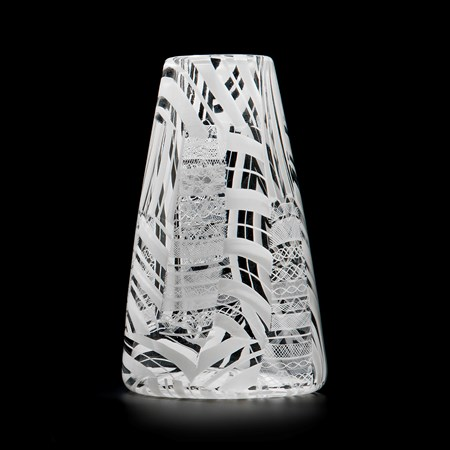 clear glass sculpted vessel with white patterned exterior