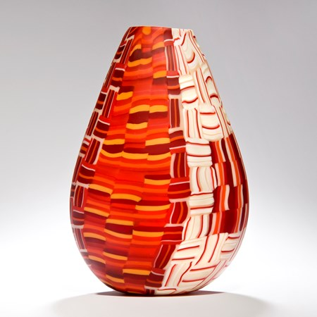 sculpted teardrop shaped glass vessel with crossing line pattern in white orange and burgandy