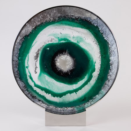 glass and steel sculpted circle with green silver and black swirls forming pattern of an eye