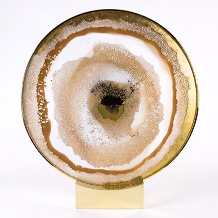 round glass art sculpture in earthy white yellow brown and gold resembling pattern of an eyeball sat on steel bezel