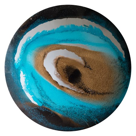 round glass art sculpture of eye-like shape in shades of blue and sand