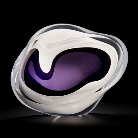 minimalist art glass sculpture of a rock in white with purple and black centre