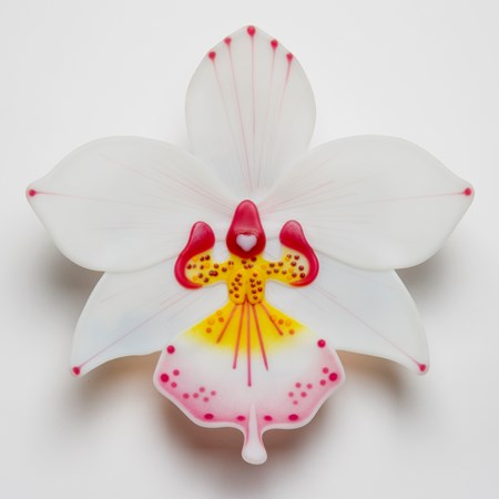 sculpted glass art of a white exotic flower with pink and yellow detail