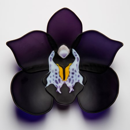 sculpted glass artwork of a black and dark purple flower with lighter detail in centre