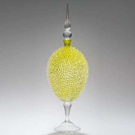 glass sculpture of spiked yellow ball in the centre of clear glass base and top