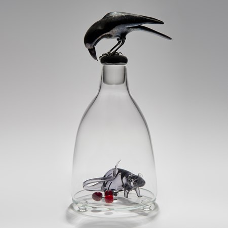 glass and steel sculpture of a mouse trapped in a clear glass flask with a crow peering in from the top
