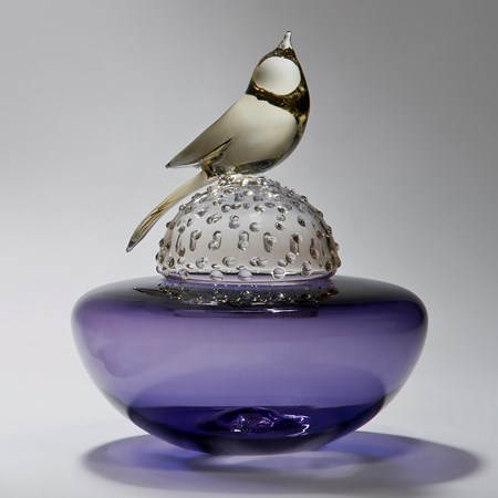 glass artwork of a light grey bird resting on a bright purple funeral urn