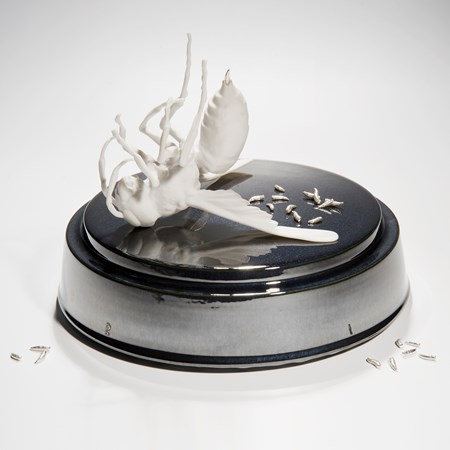 ceramic and metal sculpture of bird and maggots on round base
