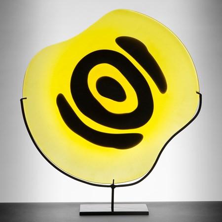 yellow rounded glass sculpture with black painted eye on metal stand