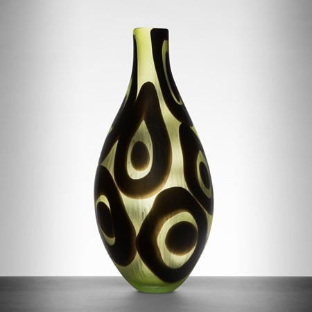 modern glass art sculpted vessel with thin neck in light green with black circle pattern