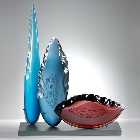 blue steel and plum glass cloves in different heights and shapes on grey glass base