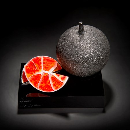 black and orange art-glass sculpture of fruit on acrylic base