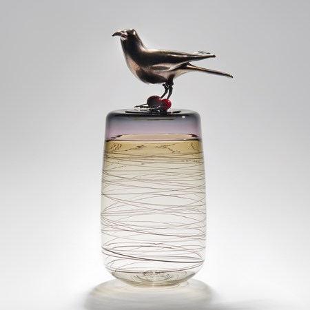 sculpted clear glass vase with angled lines circling exterior with stainless steel crow sitting atop with cherries at its feet