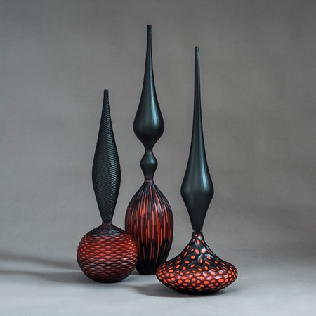 red and black contemporary geometrically patterned set of three sculptures made from handblown and cut glass