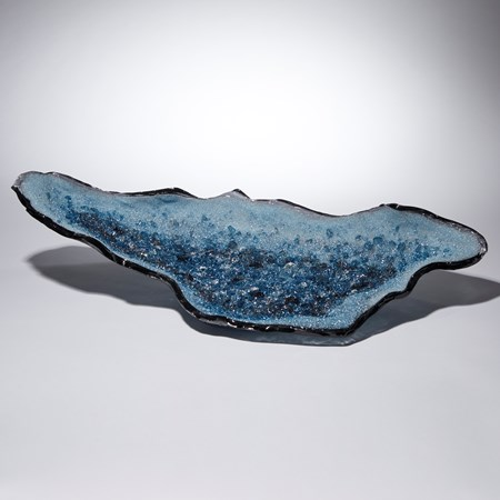 light and dark blue long organically shaped glass sculpture with a twinkling crystal covered interior