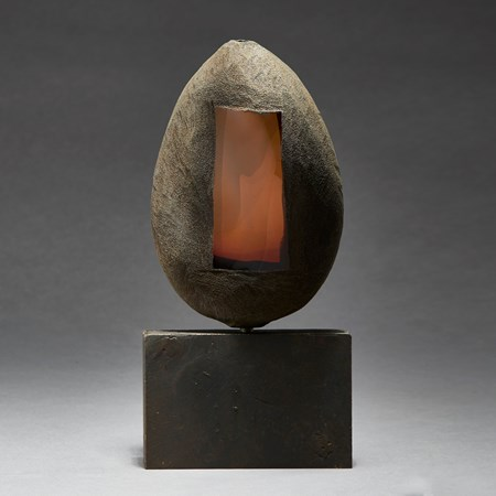 grey and brown hand made ovoid shaped glass and metal sculpture with square geometric aged metal base and rectangular orange glass window
