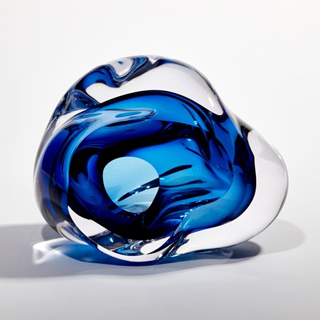 sculptural blob of handmade glass undefined in form with blue interior and clear exterior