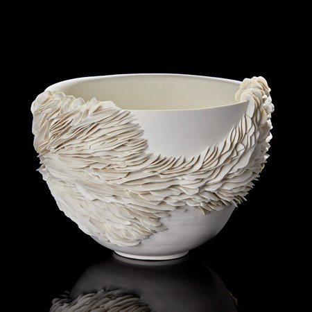 white deep wide bowl with the exterior partially covered in organic fins and ridges handmade from porcelain