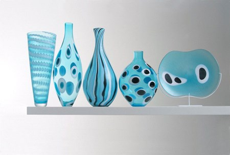 five glass vase sculptures of different sizes in aqua blue